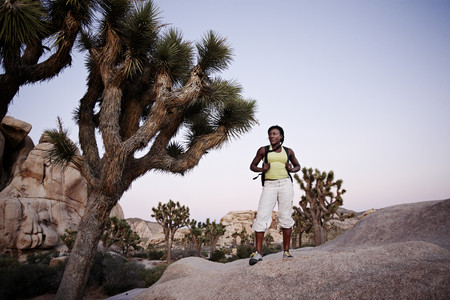 Woman hiking on large rock 免版税图像