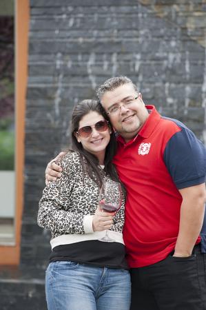 Hispanic couple drinking wine and hugging