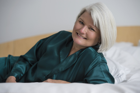 Smiling Caucasian woman laying in bed