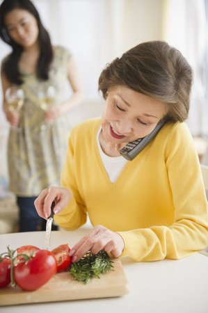 Japanese woman cutting vegetables and talking on telephone Stock Photo