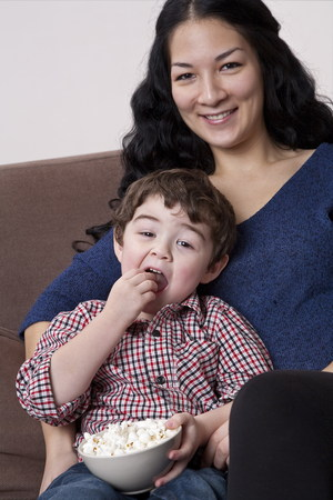 Mixed race mother and son eating popcorn