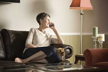 Senior woman sitting on sofa talking on telephone Stock Photo - 107970415