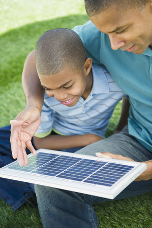 Father and son looking at solar panel Stock Photo
