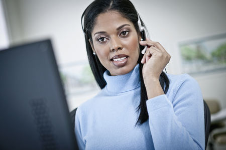Serious businesswoman working at desk in headset