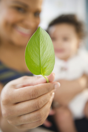 Mixed race woman holding baby and green leaf