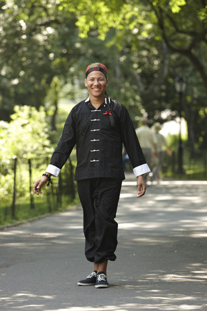Man in traditional Asian clothing walking in park