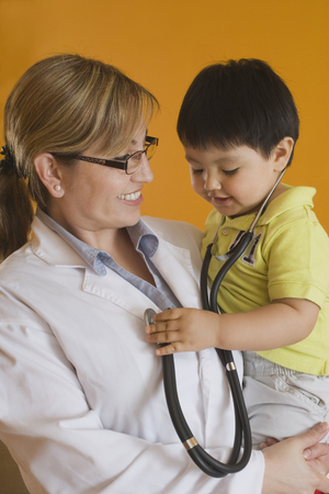 Hispanic doctor holding baby boy