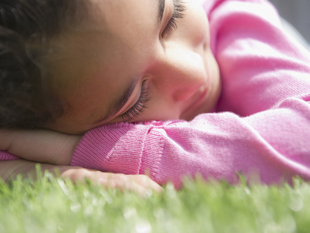 Mixed race girl sleeping in grass