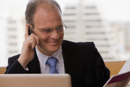 Chilean businessman talking on cell phone at desk Stock Photo