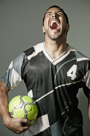 Laughing athlete holding soccer ball Stock Photo