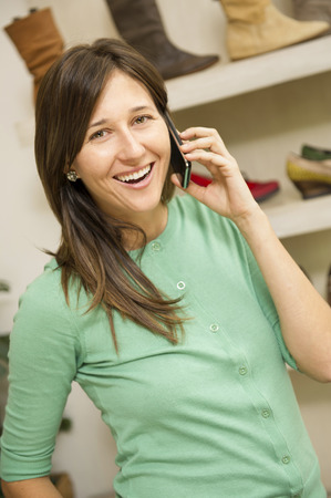 Hispanic woman talking on cell phone in shoe store Stock Photo