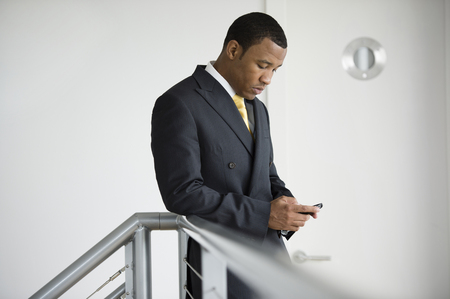 Mixed race businessman text messaging on cell phone Stock Photo
