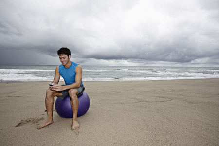 Young man sitting beach text messaging on cell phone