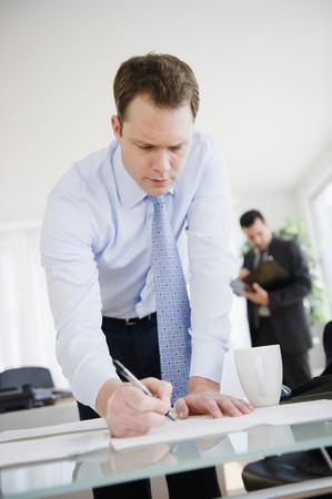 Caucasian businessman leaning on desk and writing