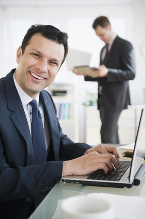 Smiling mixed race businessman using laptop
