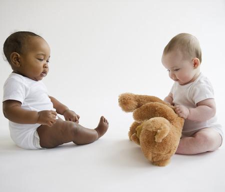Bebés sentados juntos en el piso con osito de peluche
