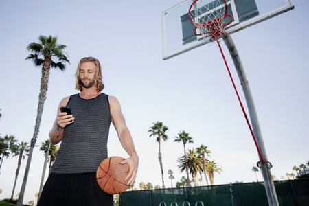 Caucasian man holding basketball and text messaging on cell phone Stock Photo
