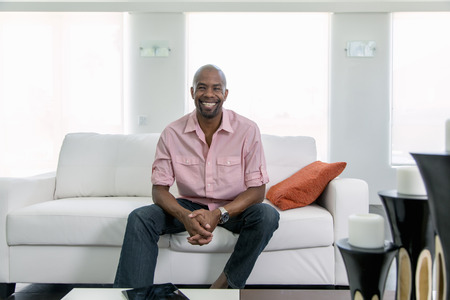 Smiling Black man sitting on sofa