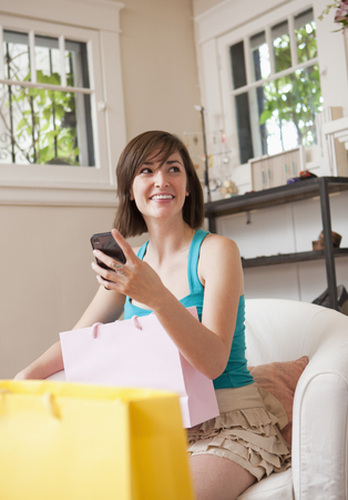 Hispanic woman sitting with shopping bags and cell phone Stock Photo