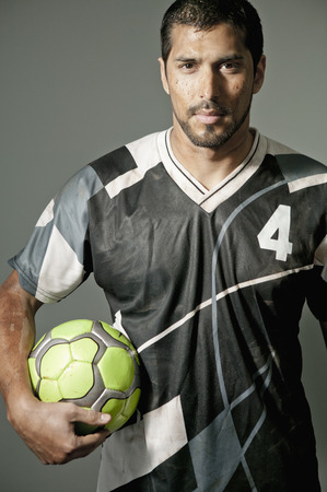 Serious athlete holding soccer ball Stock Photo