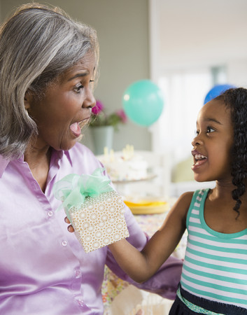 African American girl giving grandmother a gift
