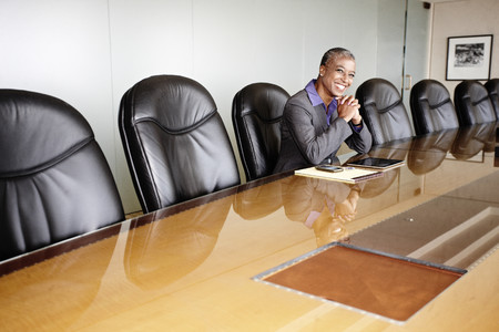 Black businesswoman sitting in empty conference room Stock Photo