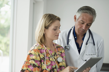 Doctor and nurse looking at digital tablet Stock Photo