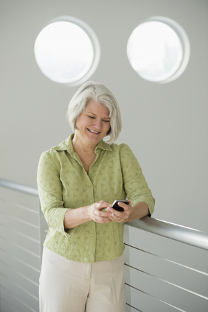 Caucasian woman text messaging on cell phone Stock Photo