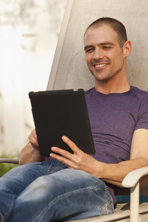 Caucasian man using digital tablet outdoors Stock Photo