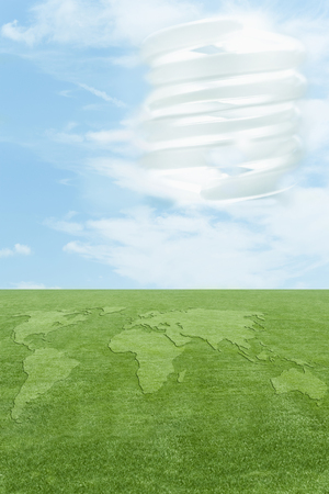 Continents in green grass, CFL light bulb in sky Фото со стока