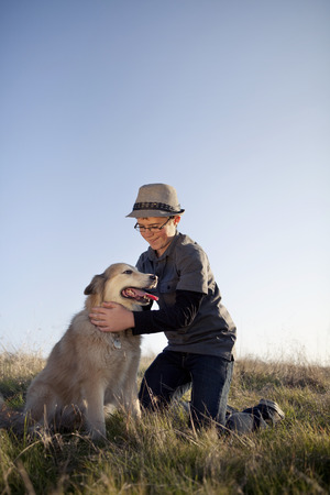 Caucasian boy petting dog in field