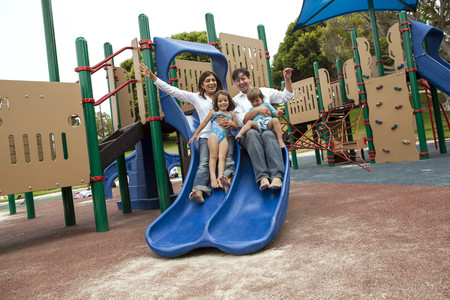 Family sliding down slide on playground