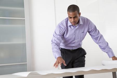 Black architect looking at blueprints Stock Photo