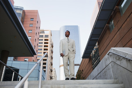 African American businessman standing at top of stairs Stock Photo