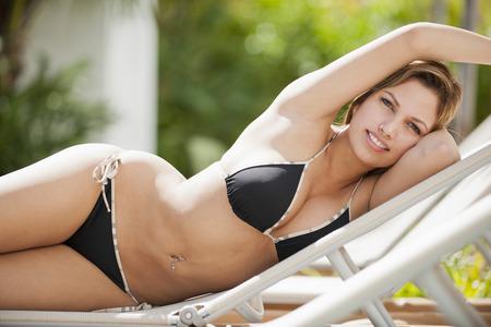 Colombian woman in bikini laying on lounge chair Stock Photo