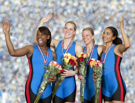 Women athletes with medals holding flower bouquets