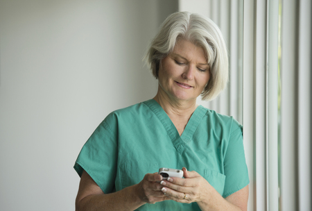 Caucasian surgeon in scrubs using cell phone