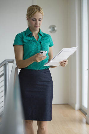 Caucasian businesswoman with paperwork and cell phone