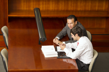 Hispanic businessmen working in conference room Stock Photo