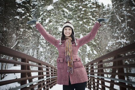 Smiling Caucasian woman standing on bridge in snow