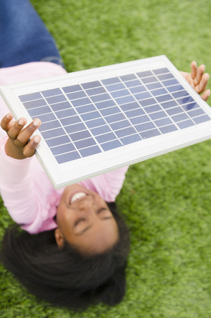 Black girl holding solar panel
