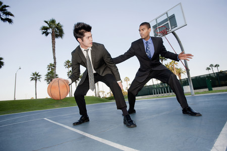 Businessmen playing basketball outdoors Stock Photo