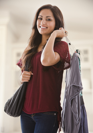 Mixed race woman holding clothing Stock Photo