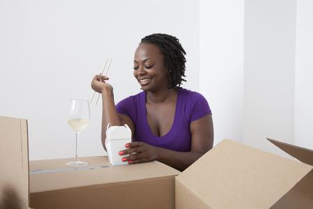 Black woman unpacking and eating Asian food