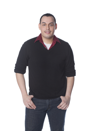 Smiling Hispanic man with hands in pockets
