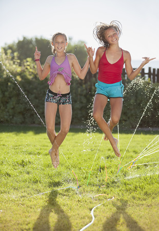 Caucasian girls playing in sprinkler