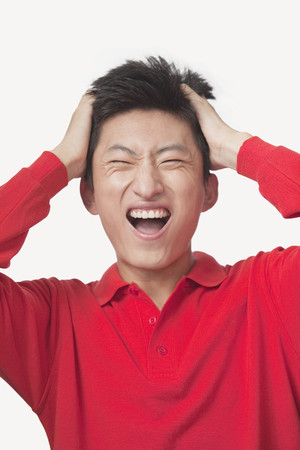 Frustrated Chinese man with head in hands
