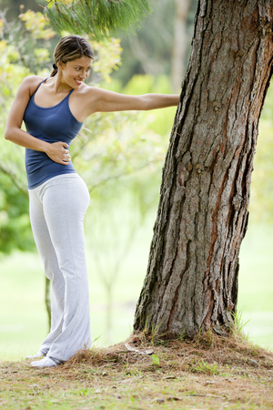 Hispanic woman leaning on tree stretching