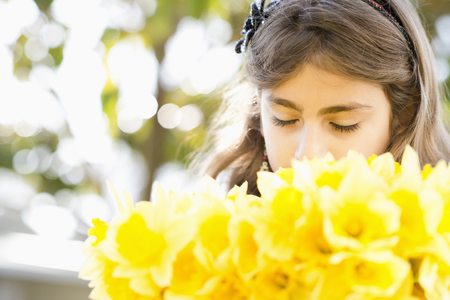 Mixed race girl smelling flowers