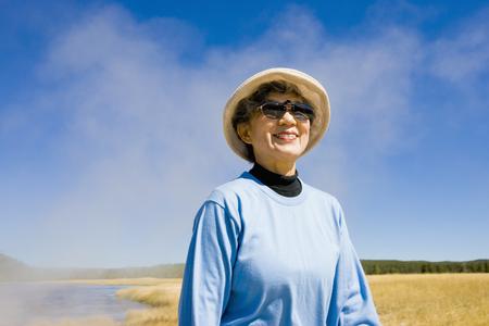 Smiling Japanese woman standing near lake